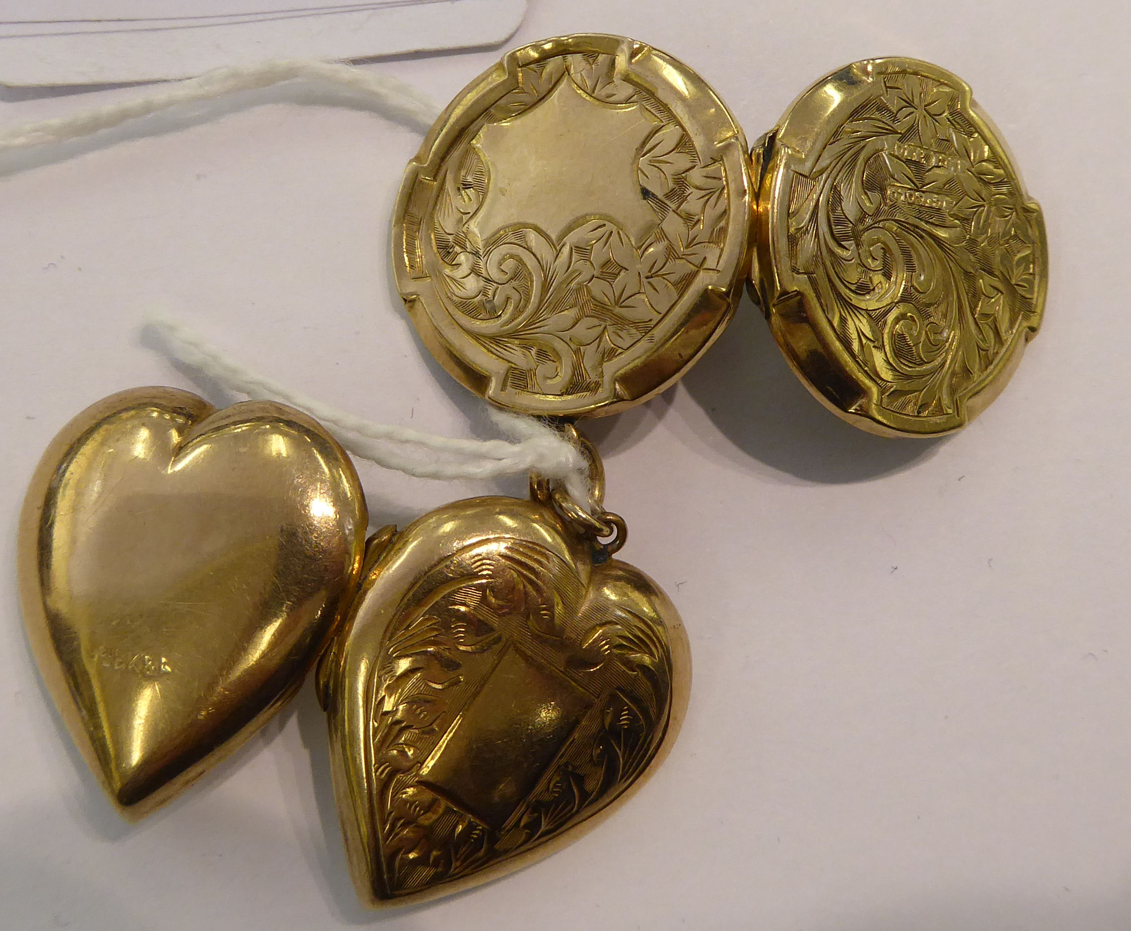 Lot 74 - Two dissimilar gold coloured metal lockets, one heart shaped,