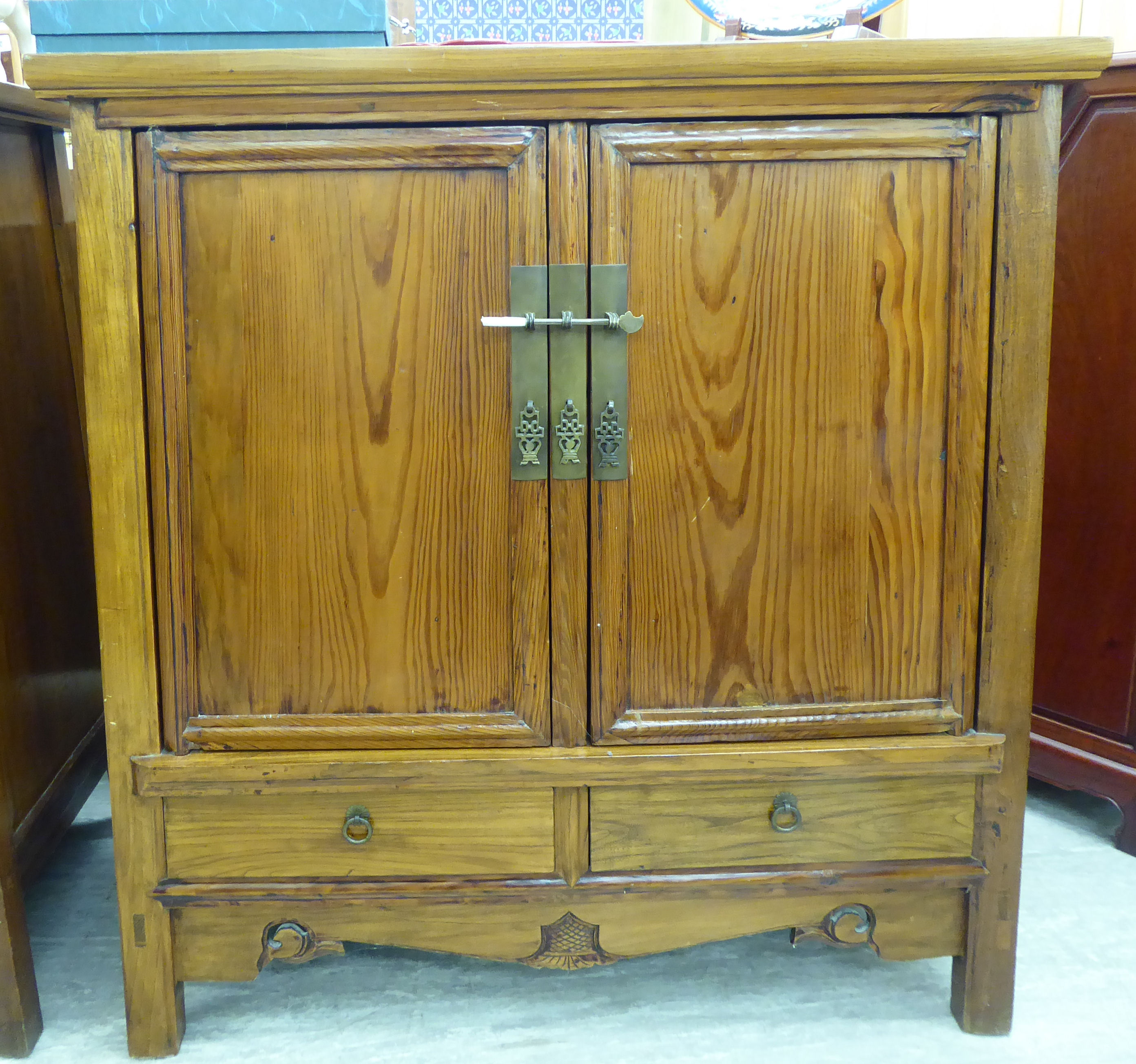 Lot 62 - A modern Chinese lacquered elm cabinet, the top with a mitred edge,