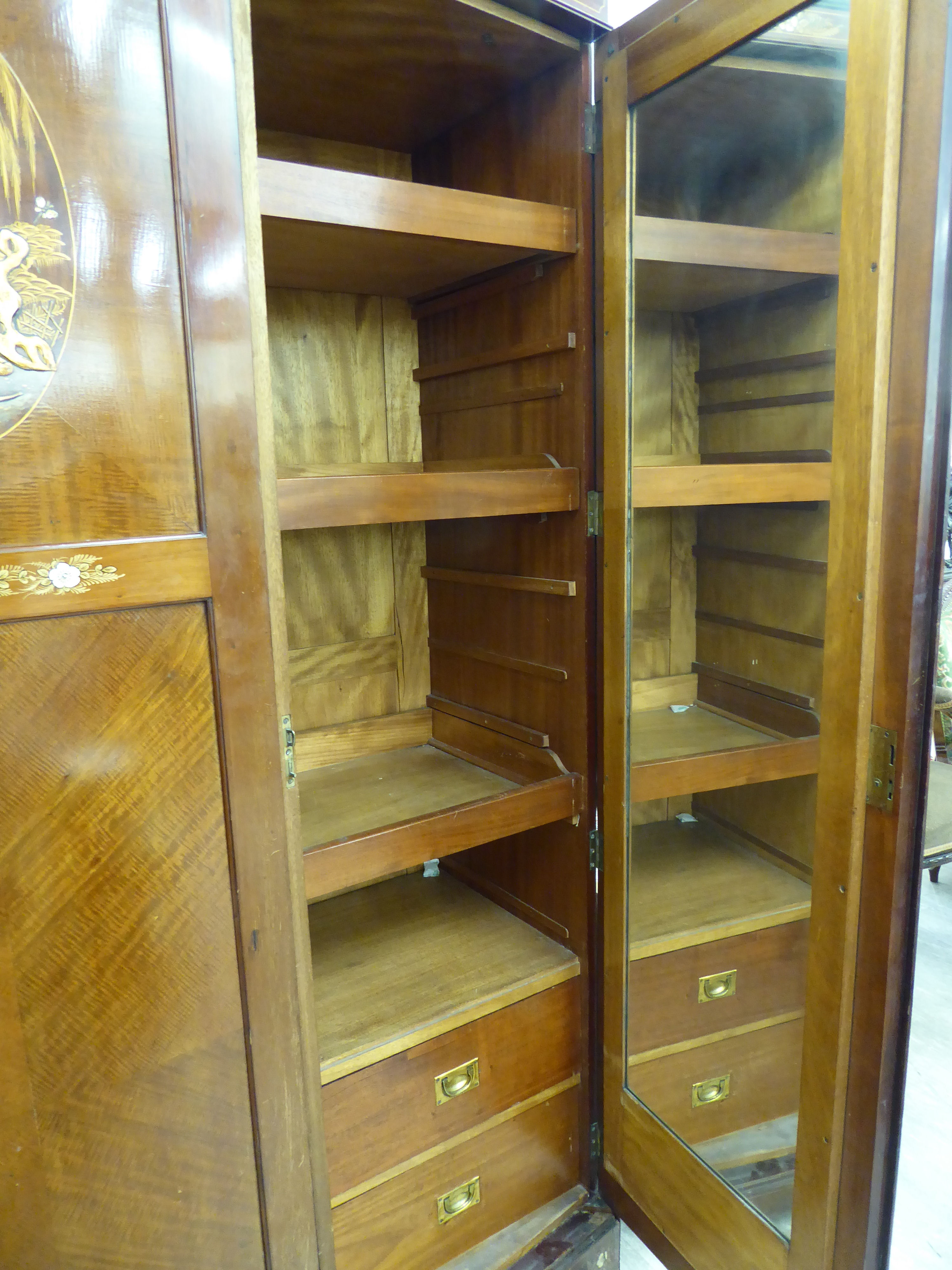 Lot 28 - A 1930s/50s mahogany bow front wardrobe, enclosing an arrangement of shelves and rails,