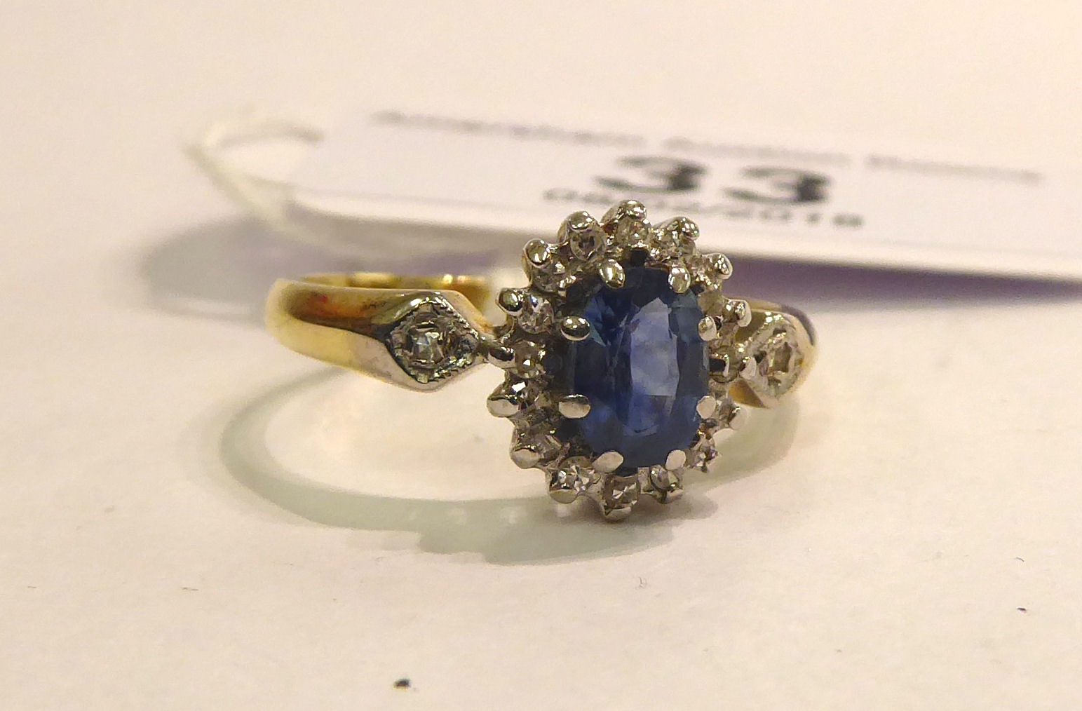 Lot 33 - An 18ct gold claw set sapphire and diamond cluster ring 11