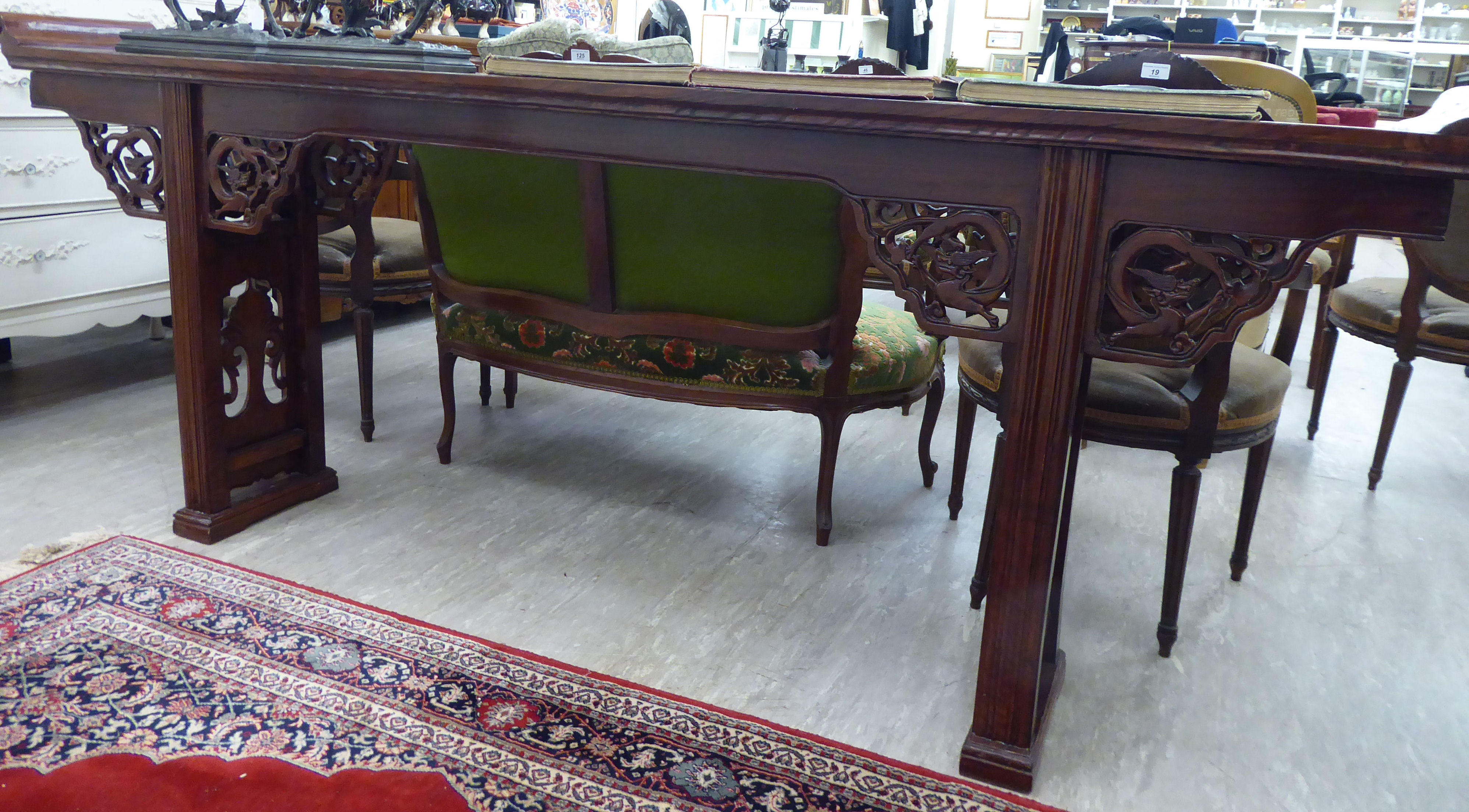 Lot 90 - A modern Chinese lacquered elm altar table, the top with raised ends, over a carved apron,
