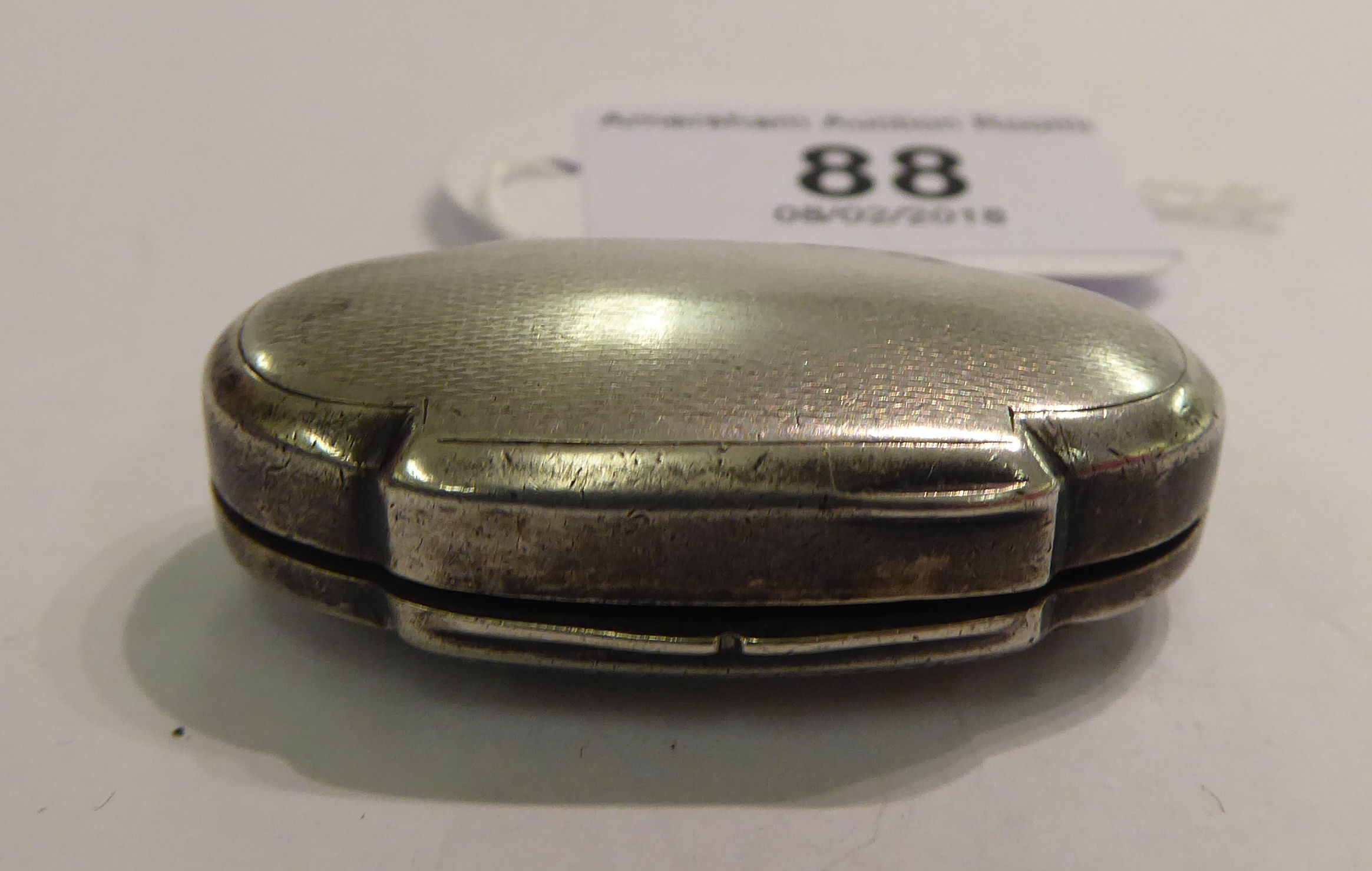 Lot 88 - A silver coloured metal oval patch box with engine turned decoration stamped 925 11