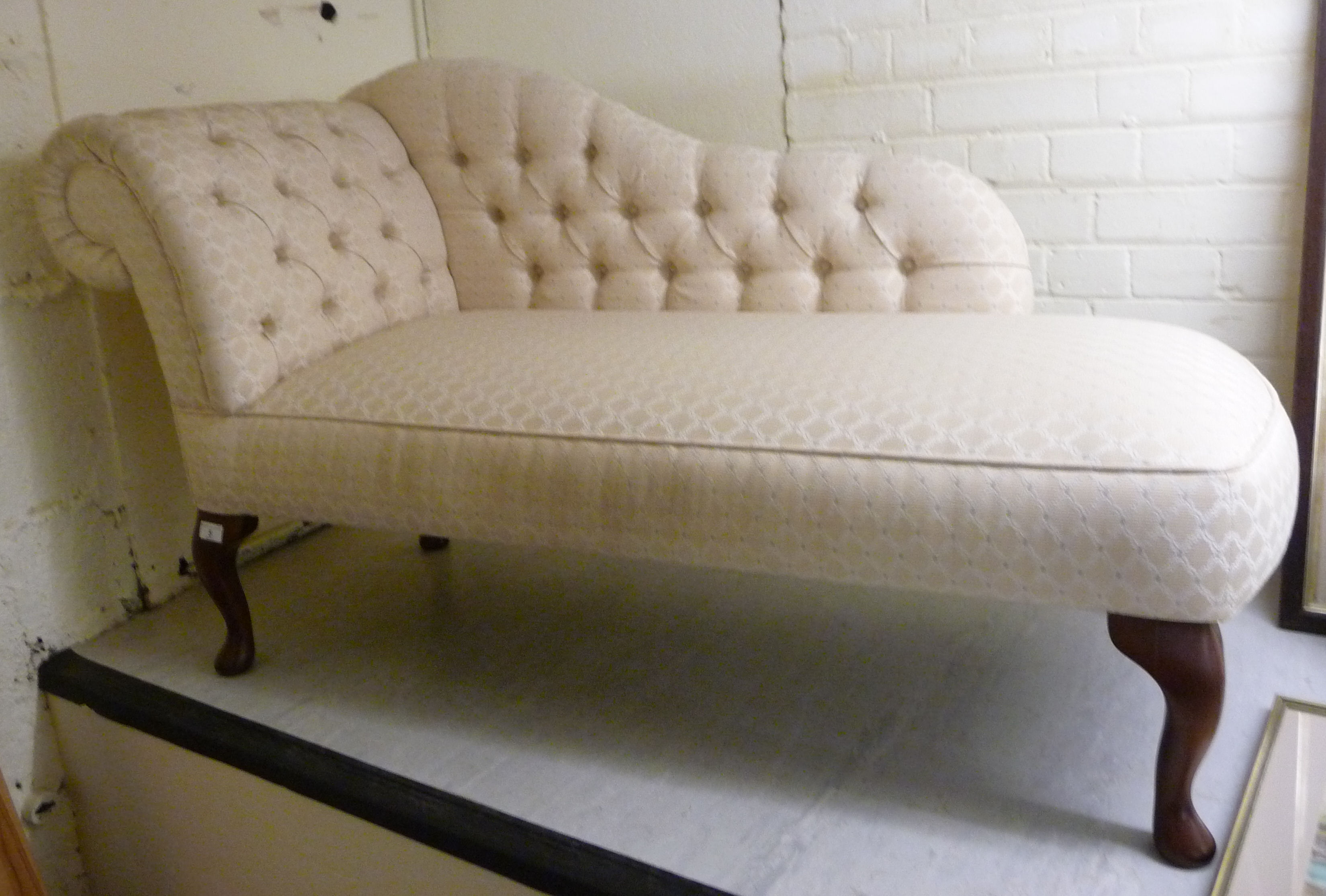 Lot 5 - A modern chaise longue, the cream coloured part-button upholstered back,