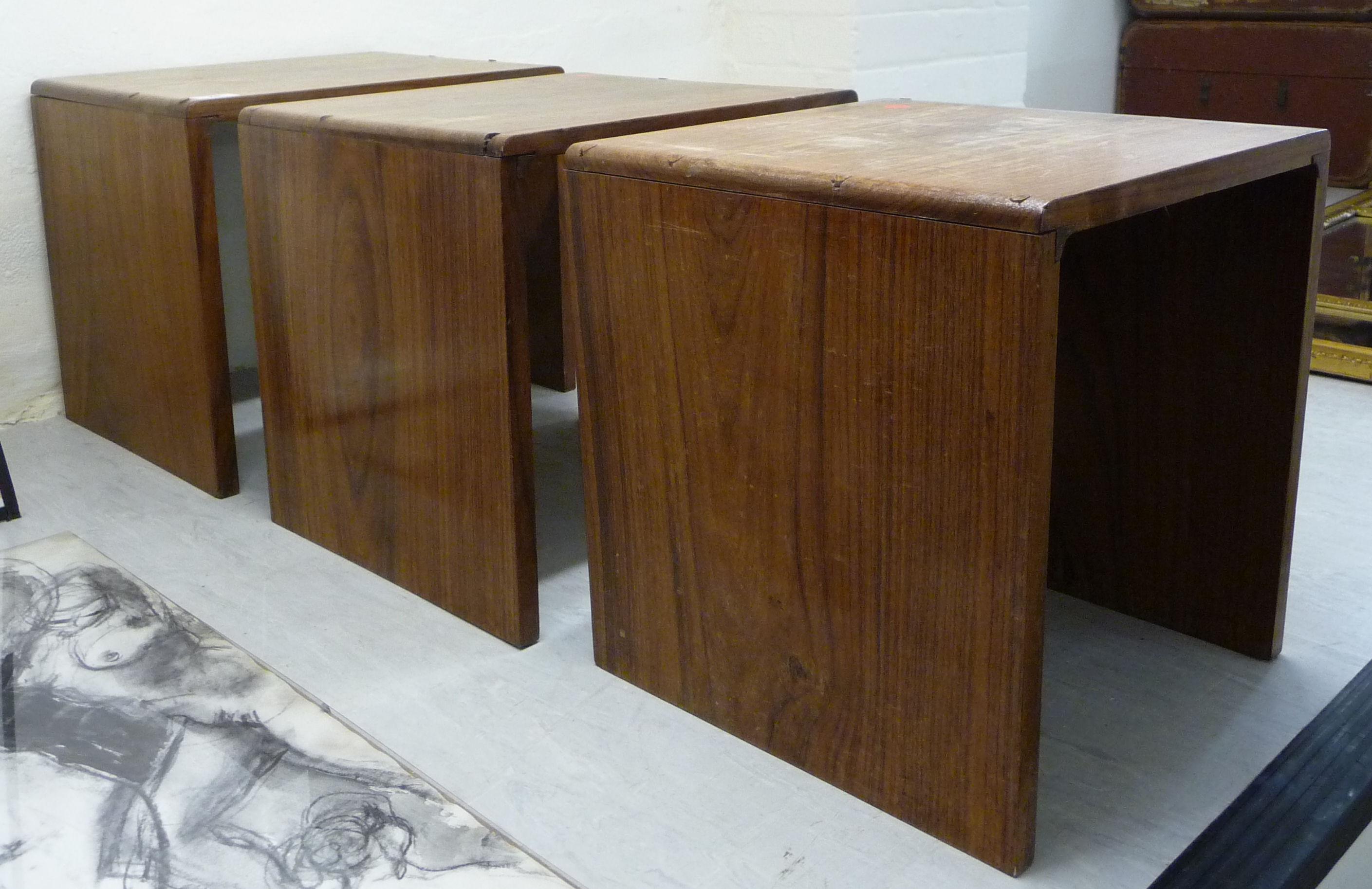 Lot 76 - A nesting set of three mid 20thC boarded teak occasional tables largest 16''h 17''w BSR
