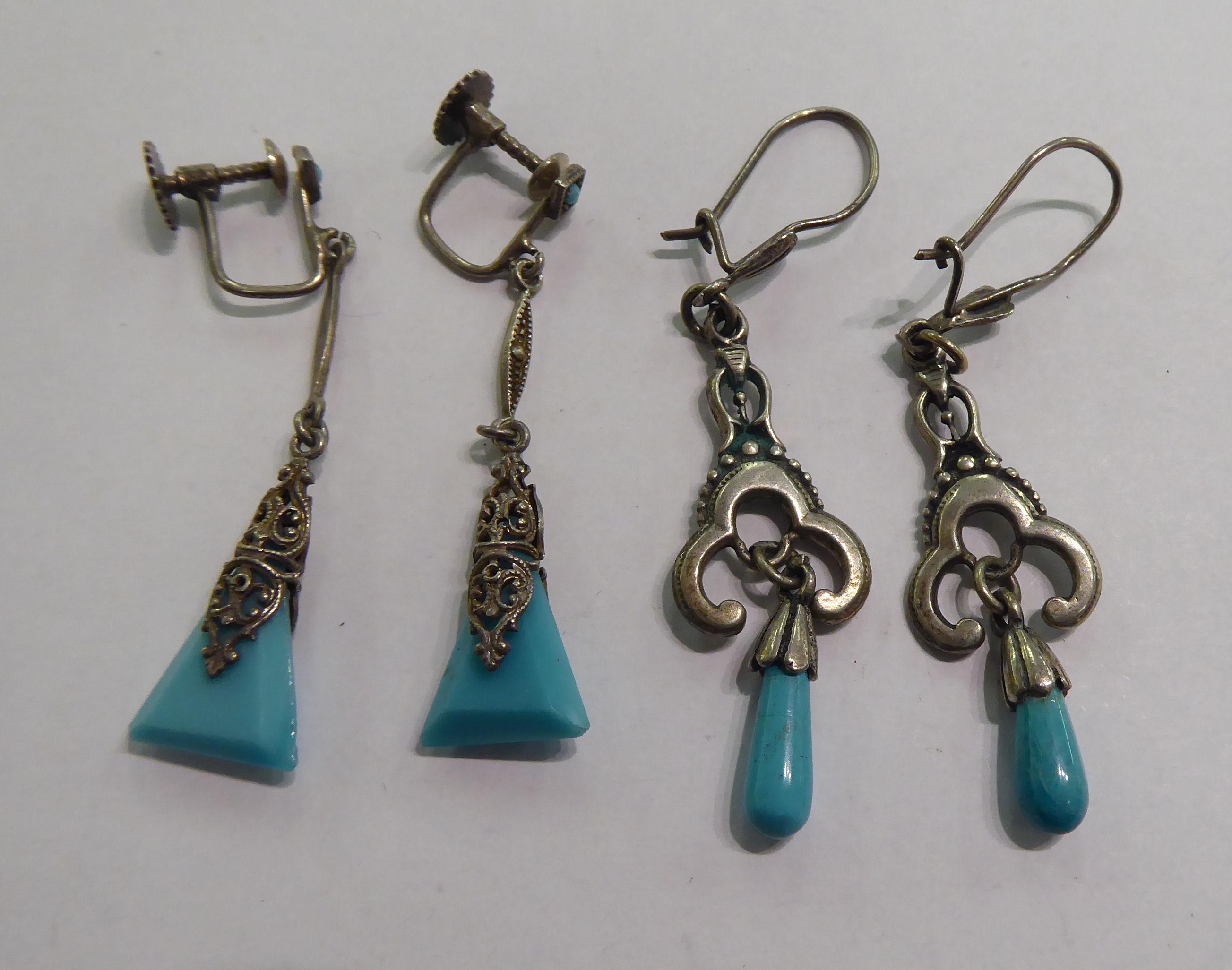 Lot 35 - Two similar pairs of white metal earrings,