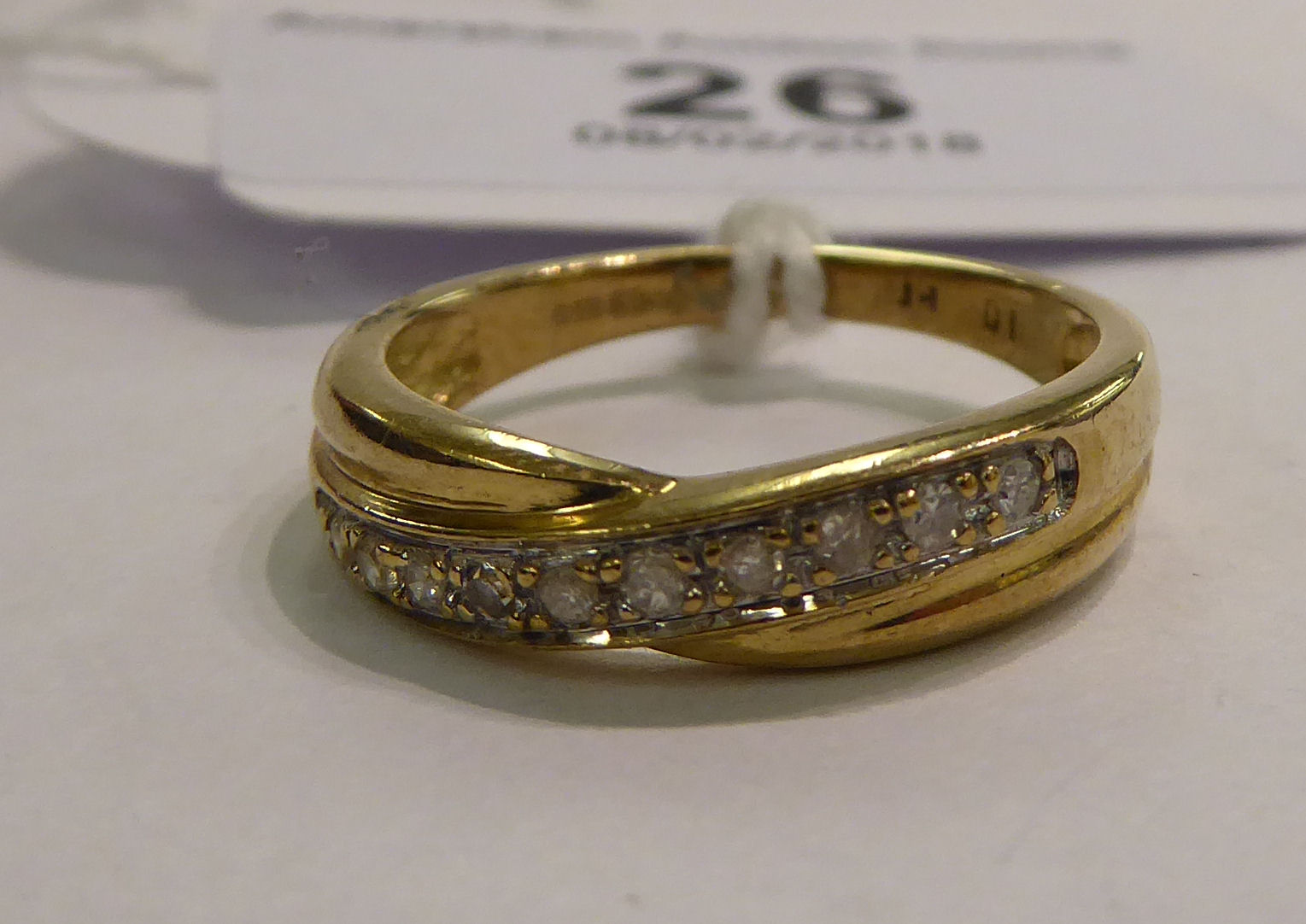 Lot 26 - A 9ct gold crossover set diamond half eternity ring 11