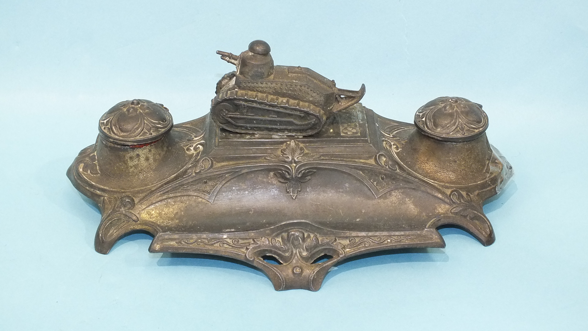 Lot 157 - A French metal inkstand surmounted by a model of a WWI tank, 20cm, (one glass liner lacking).