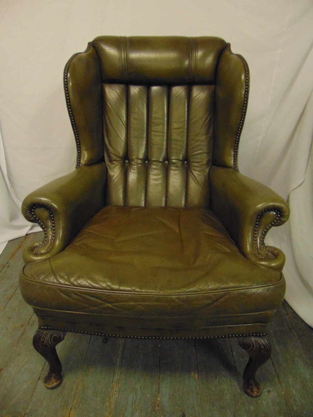 Lot 27 - A green leather armchair, button back on scroll legs