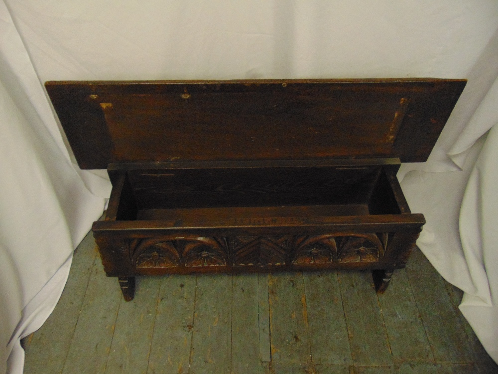 Lot 18 - A rectangular oak monks bench with carved sides, hinged cover on four turned legs