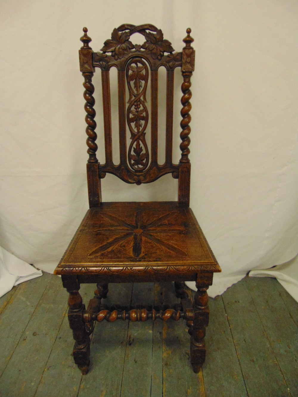 Lot 37 - A continental oak hall chair carved and pierced on turned legs