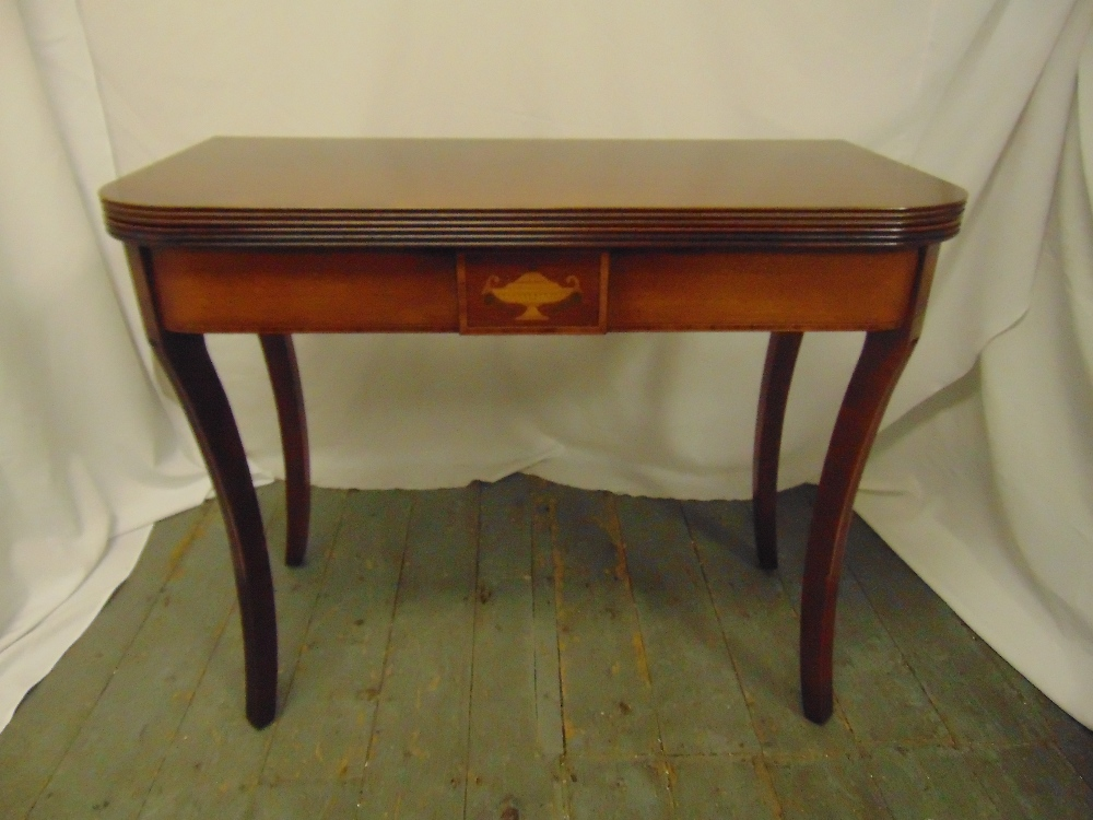 Lot 14 - A rectangular mahogany games table with hinged top revealing a green baize on four sabre legs