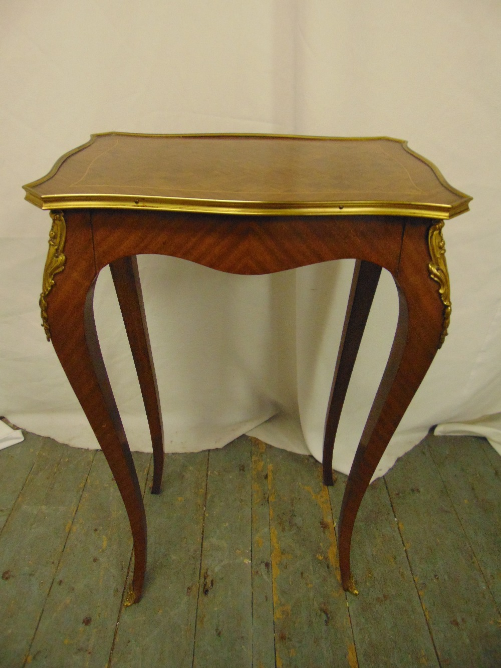 Lot 9 - A rectangular Kingswood side table with applied gilded metal mounts on four cabriole legs