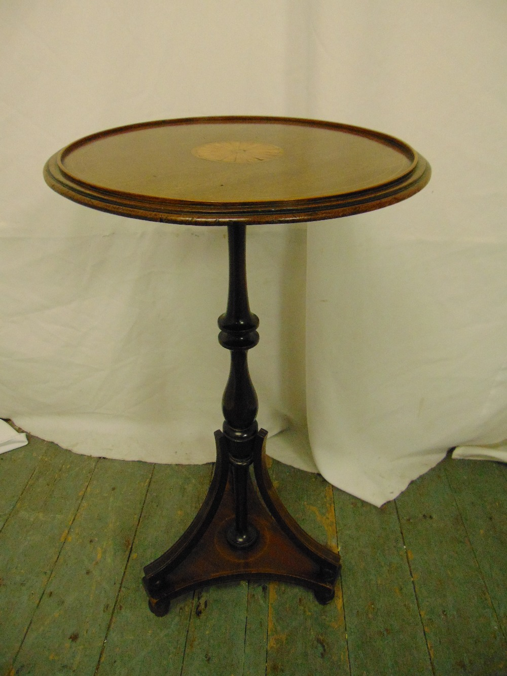 Lot 21 - An Edwardian circular mahogany inlaid side table, the knopped stem on triform support