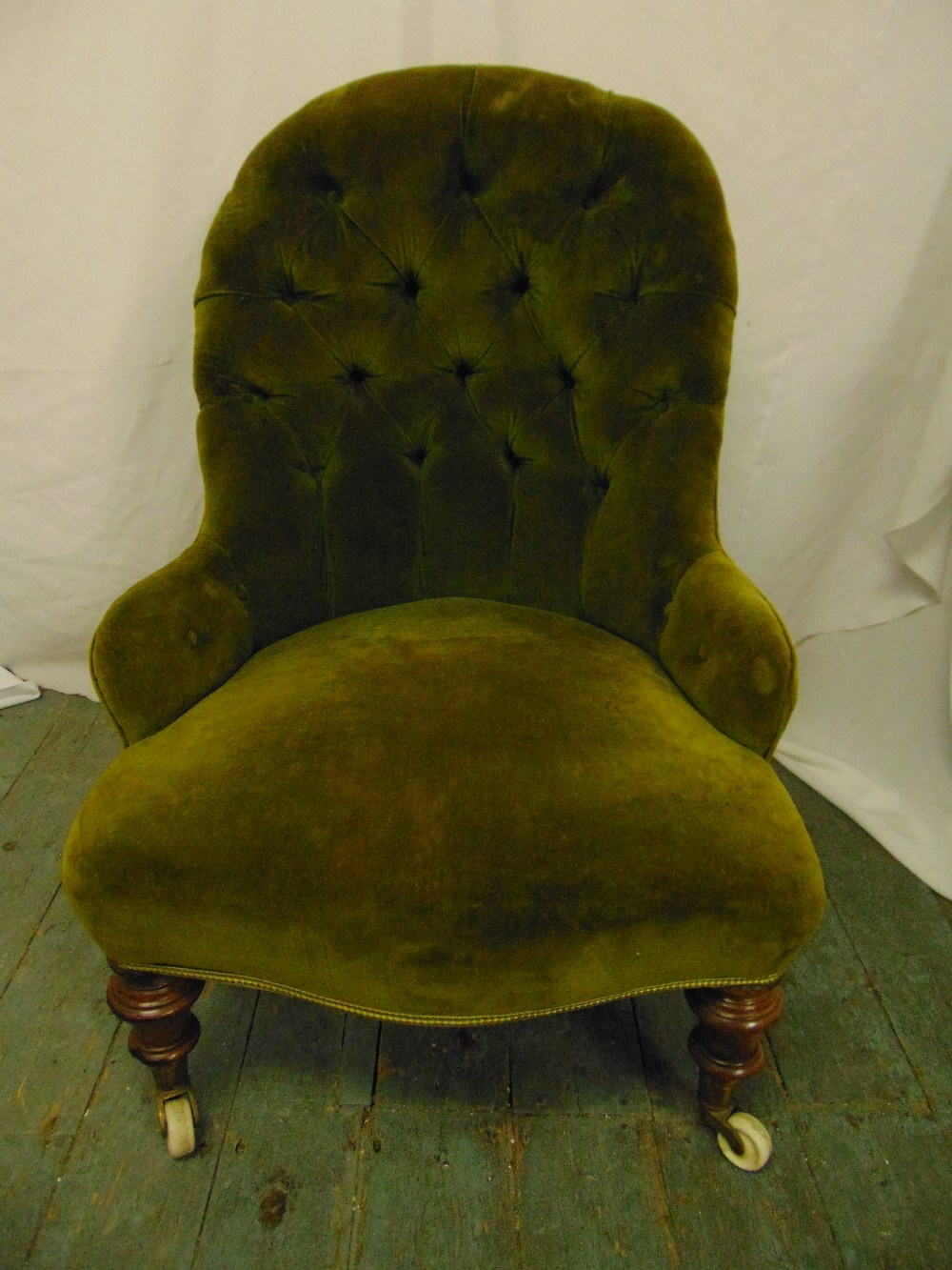 Lot 30 - A Victorian ladies button back upholstered chair on turned mahogany legs with original castors