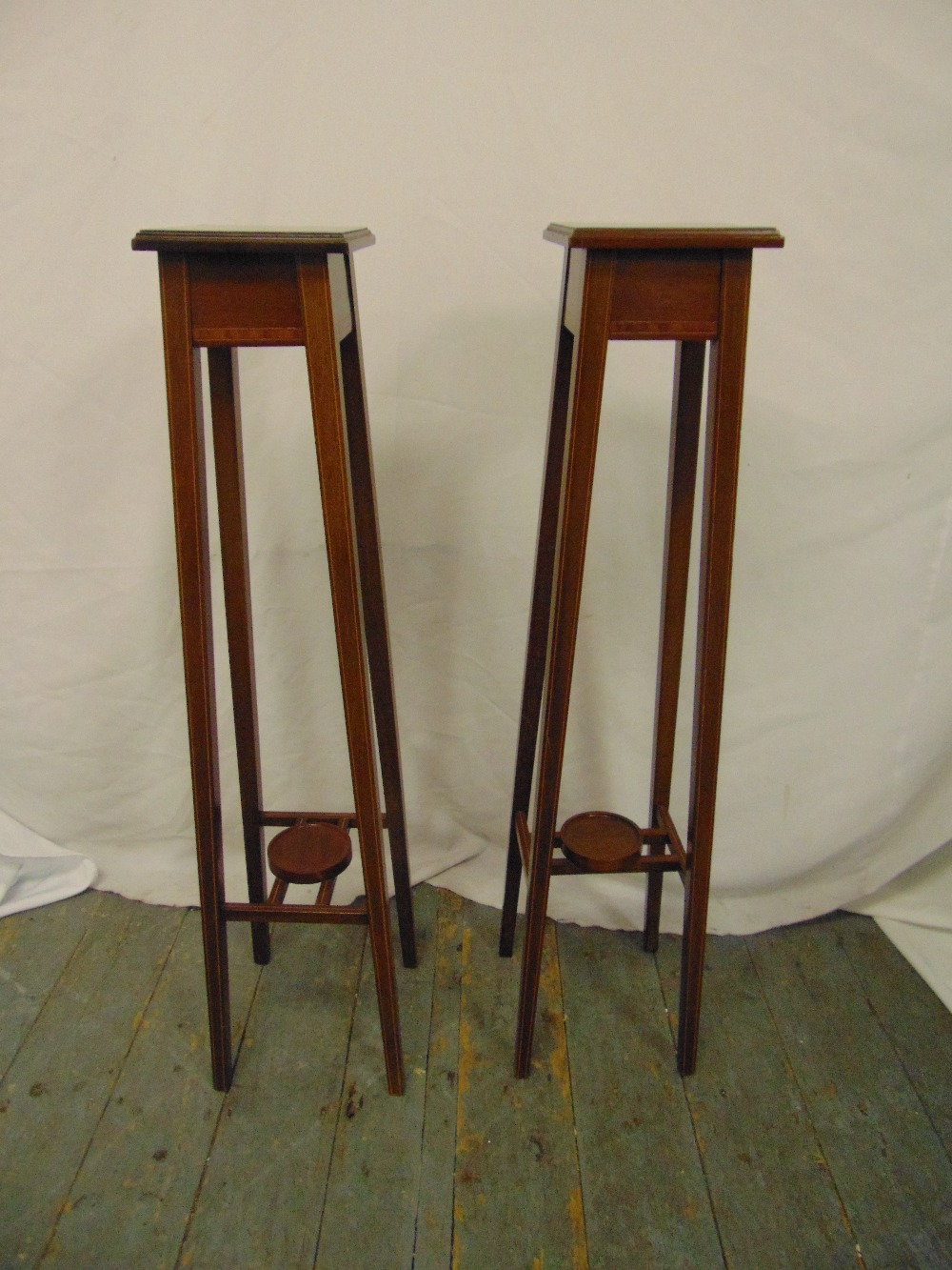 Lot 22 - A pair of Edwardian mahogany inlaid plant stands on four tapering rectangular supports