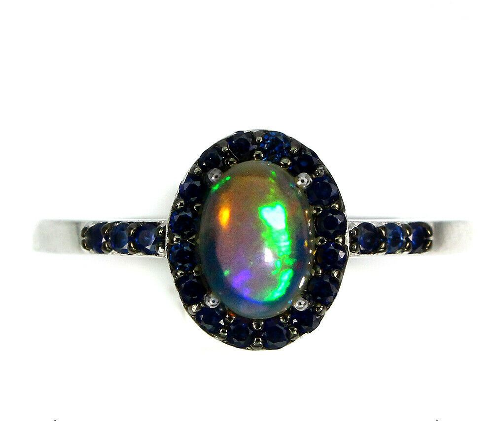 A 925 silver cluster ring set with a cabochon cut opal and sapphires, (P).