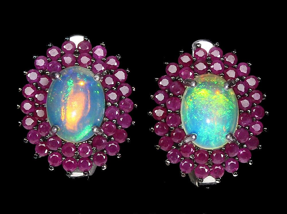 A pair of 925 silver cluster earrings set with cabochon cut opals surrounded by two rows of