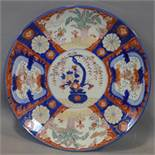 A large Japanese charger in the Imari pallette, decorated with panels of flowers, having birds to
