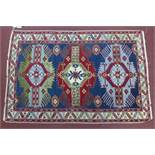 A Russian Shirvan rug, triple geometric medallions and floral motifs on a blue ground, within