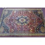 A Persian Qashqai carpet, central floral medallion and stylised petal motifs on a rouge field,