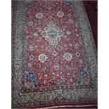 An American Sarouk rug, central floral medallion and floral motifs on a rouge field, within floral