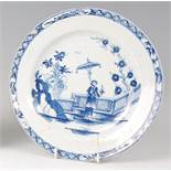 A Lowestoft porcelain plate, circa 1765, underglaze blue decorated in the Lady & Parasol pattern