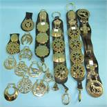 A collection of vintage and modern horse brasses, some mounted on leather straps.