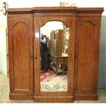 A Victorian mahogany breakfront wardrobe, the central mirror door enclosing maple drawers and
