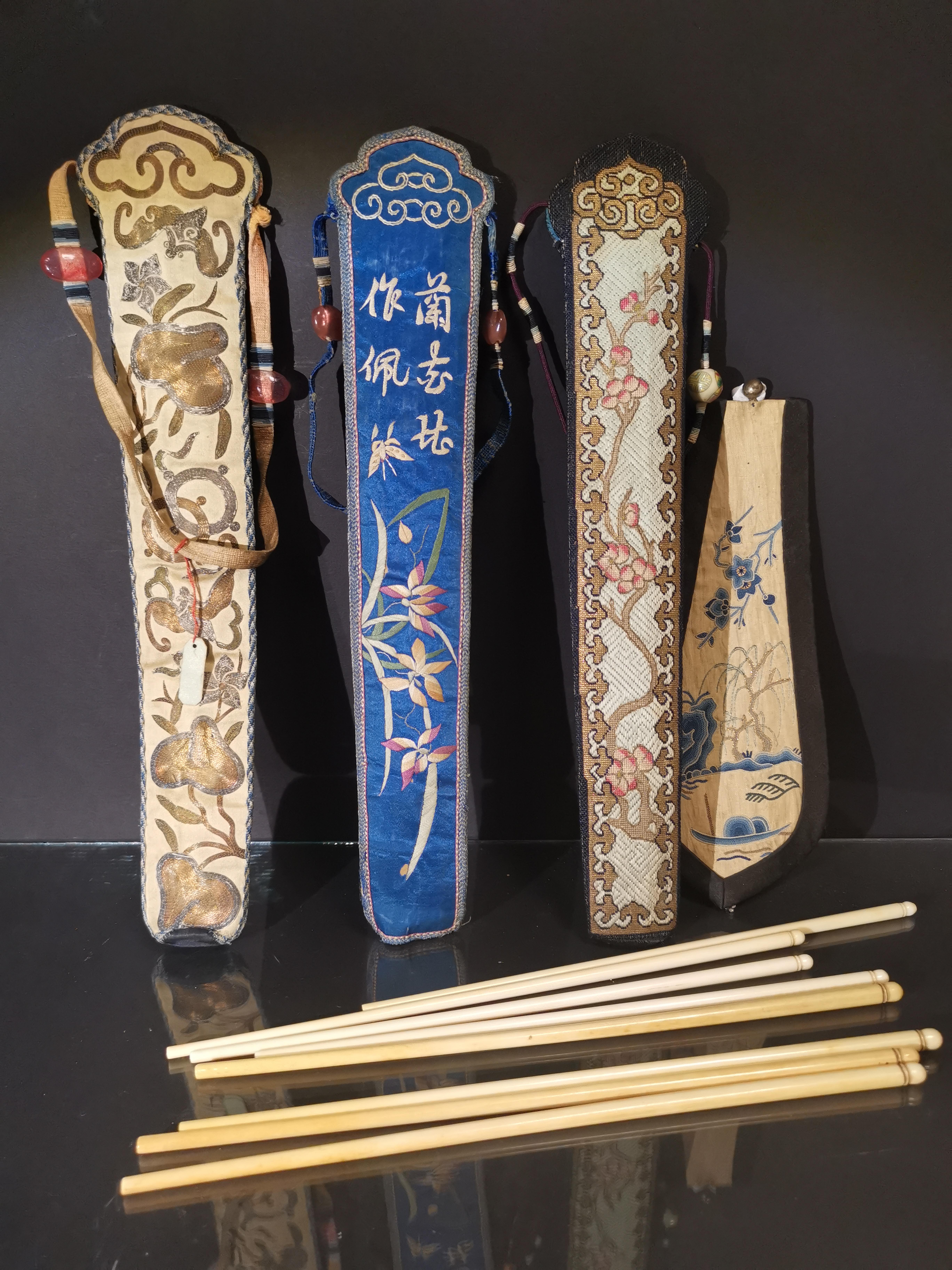 Trois étuis d'éventails en soie brodée contenant 8 baguettes et une broderie. [...]