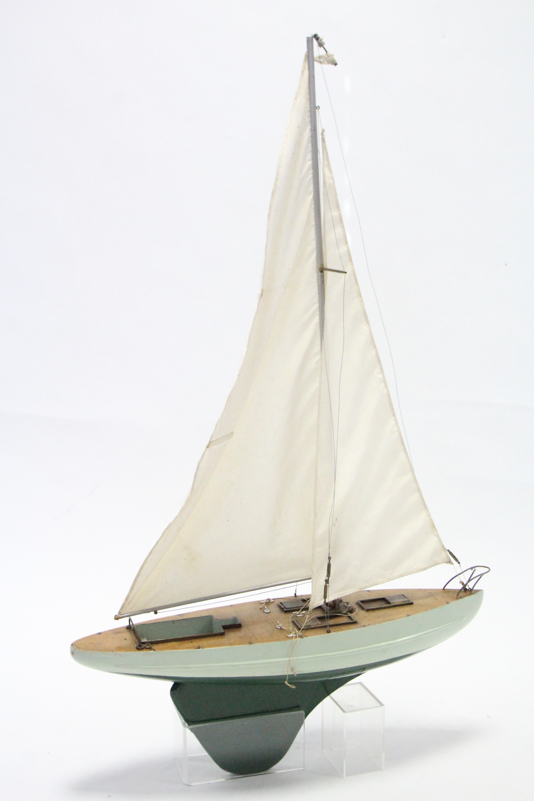 """A painted wooden pond yacht with sails, 21"""" wide."""