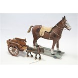 """A painted composition child's ride-on horse, 28¾"""" high; & a child's wooden pull-along horse & cart."""