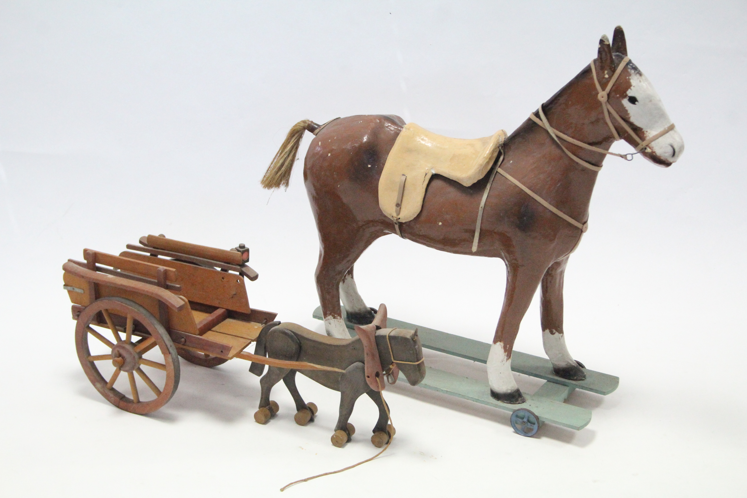 "A painted composition child's ride-on horse, 28¾"" high; & a child's wooden pull-along horse & cart."