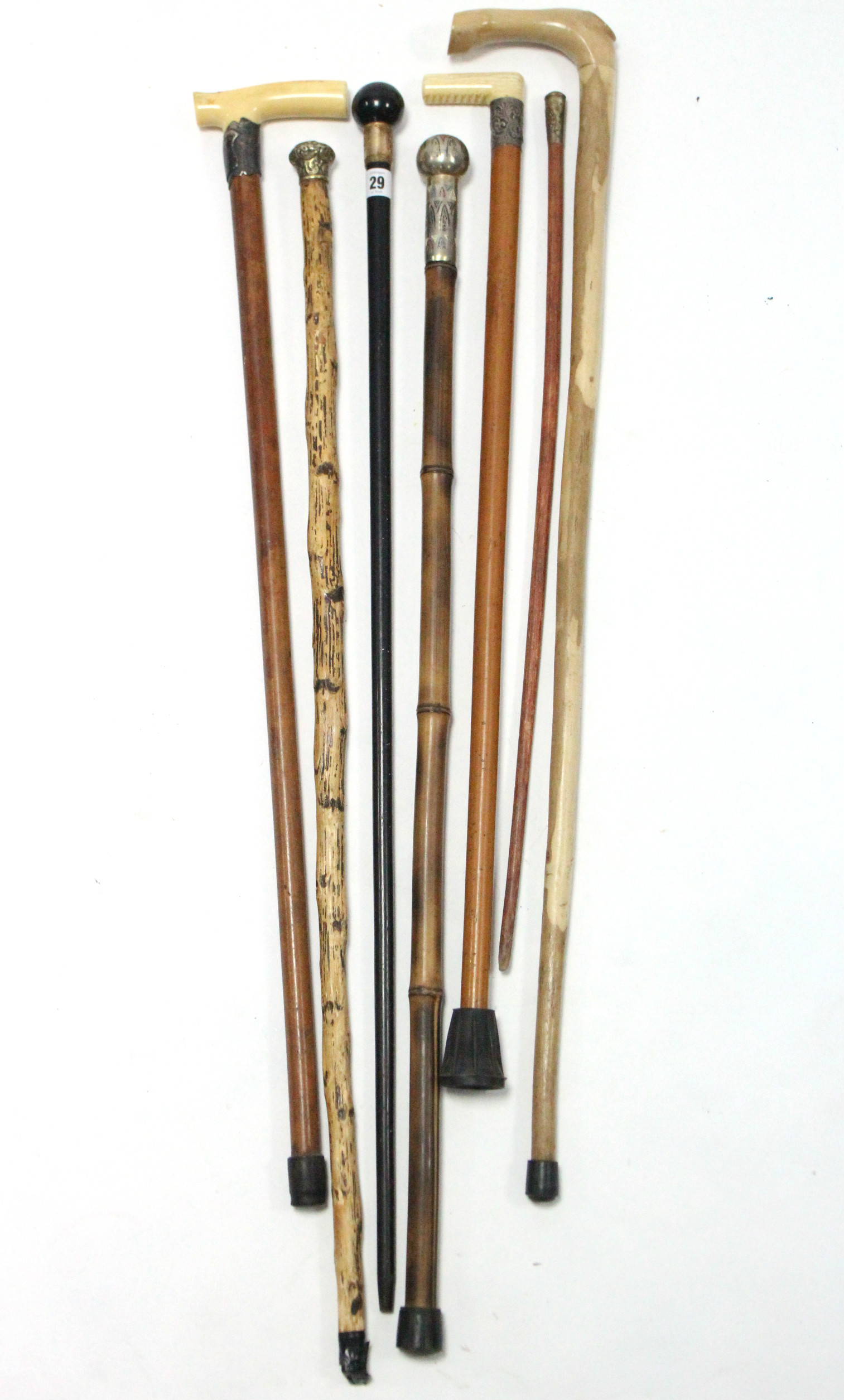 Lot 29 - An Edwardian ebonised gent's walking cane with 18ct. gold plated mount; together with five other