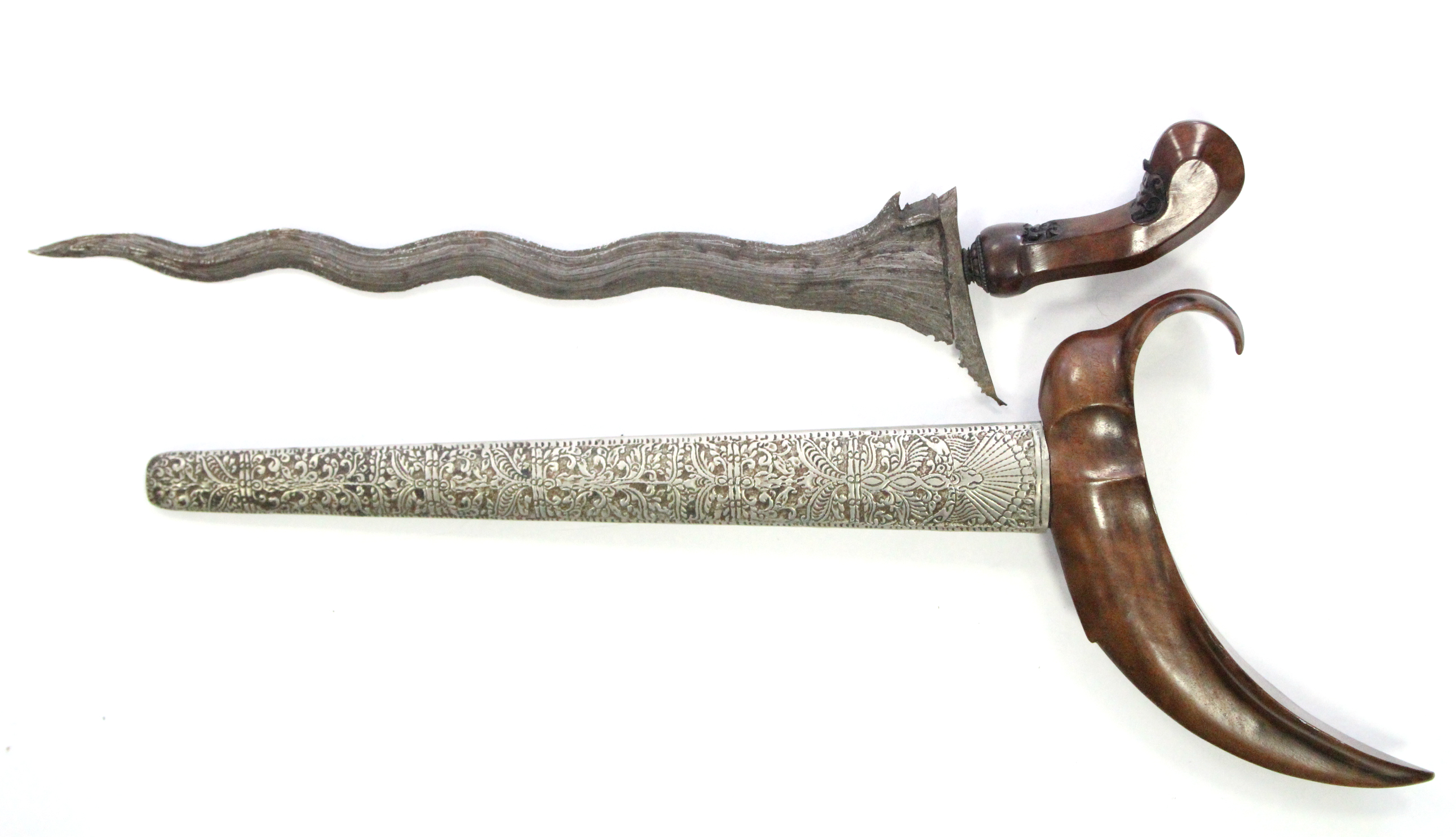"Lot 172 - An eastern kriss with 13¼"" long blade, with treen handle & engraved white-metal sheath."