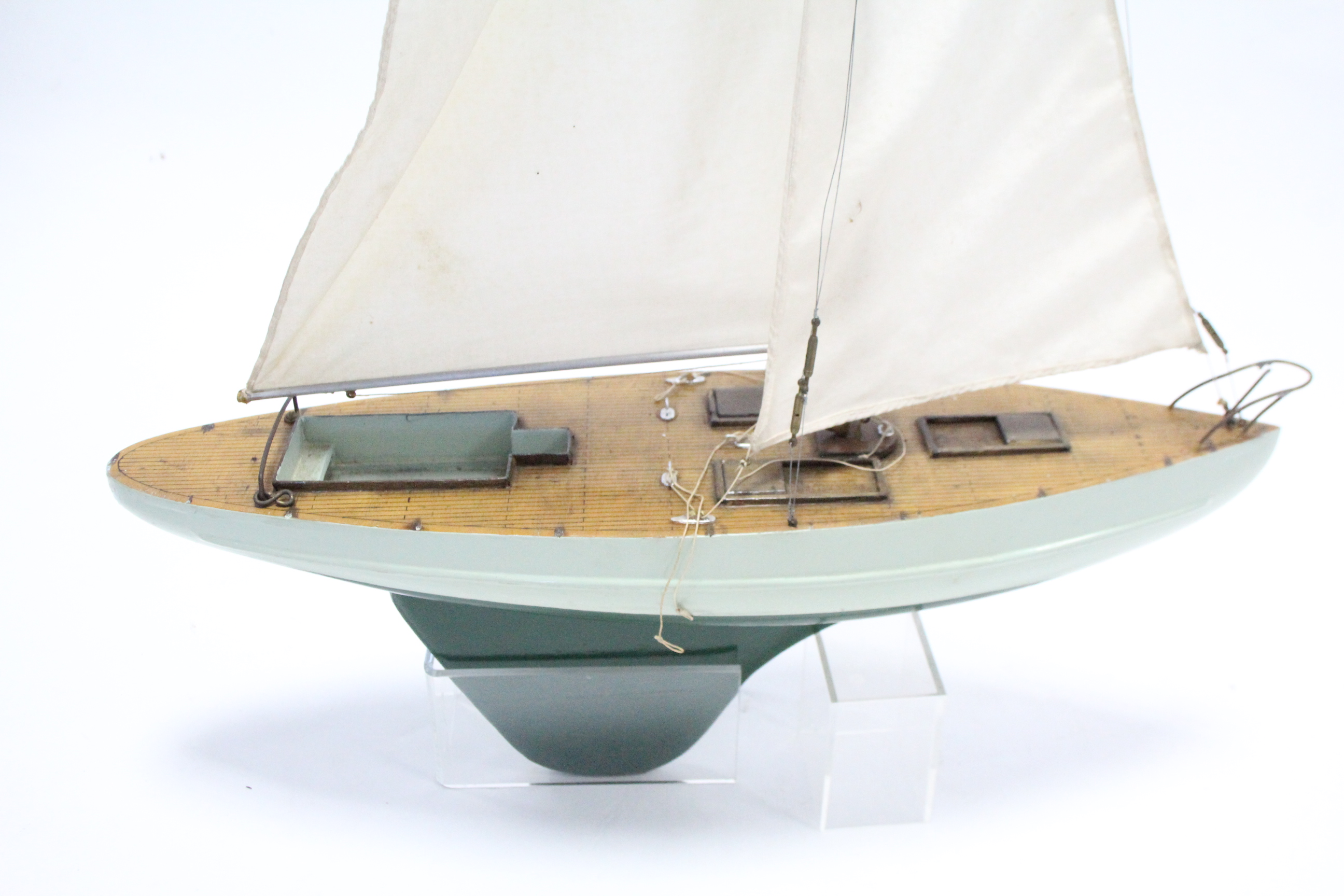 """Lot 320 - A painted wooden pond yacht with sails, 21"""" wide."""