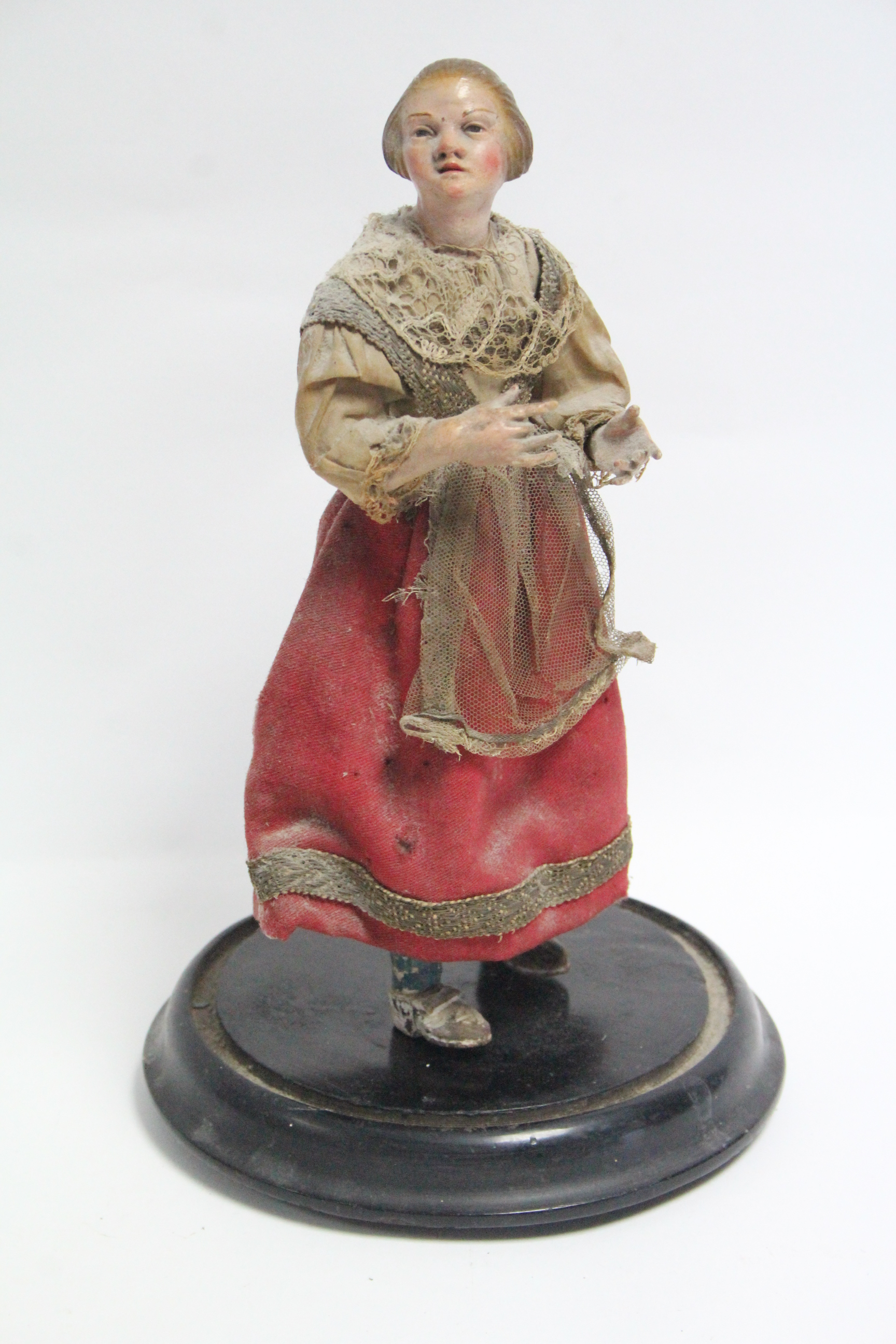 """A painted composition peddler doll mounted on ebonised wooden plinth, 11½"""" high."""