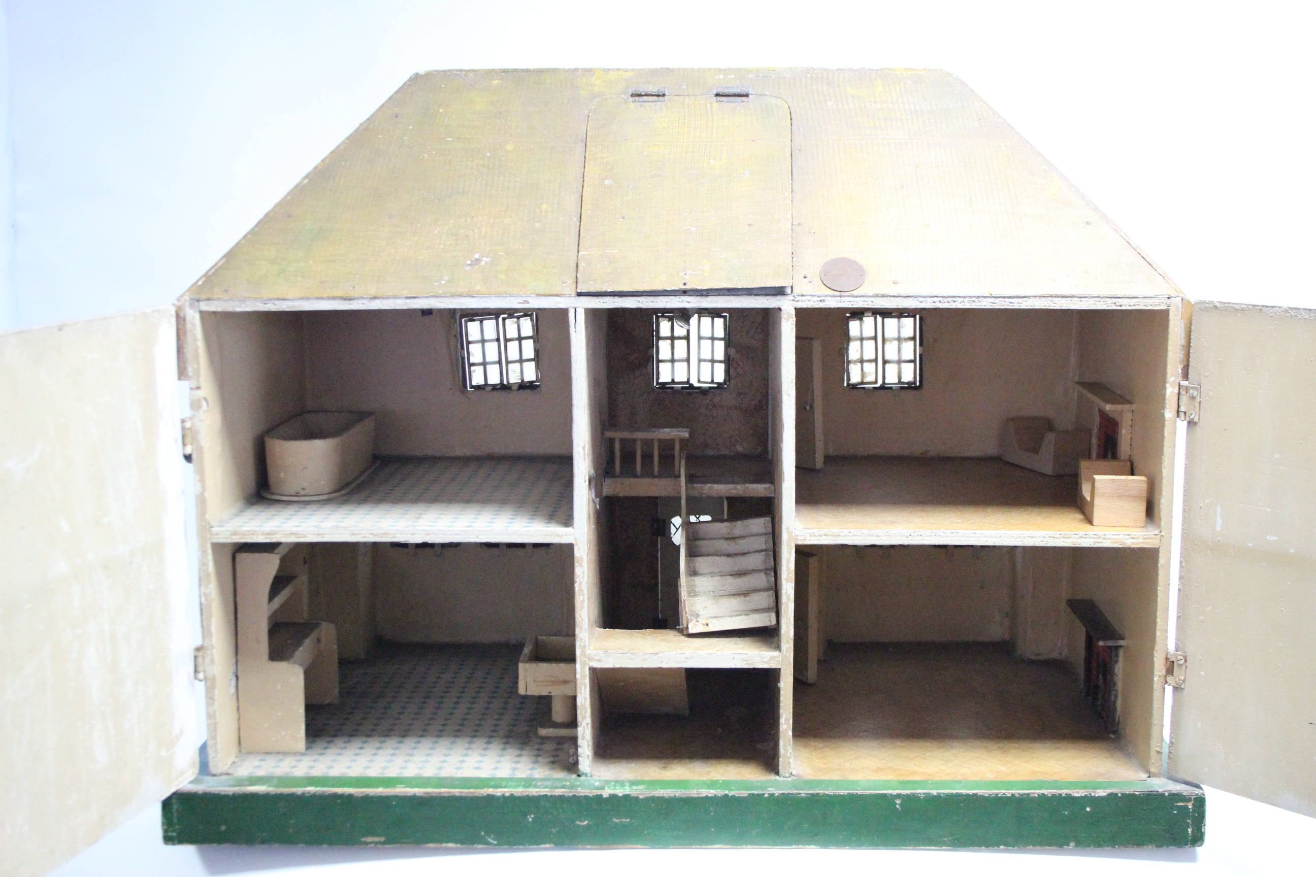 Lot 286 - An early-mid 20th century Tri-ang painted wooden cottage-style two-storey doll's house, with opening