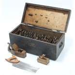 "A black painted deal tool chest, 25½"" wide, containing various carpenter's tools."