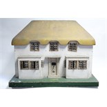 An early-mid 20th century Tri-ang painted wooden cottage-style two-storey doll's house, with opening