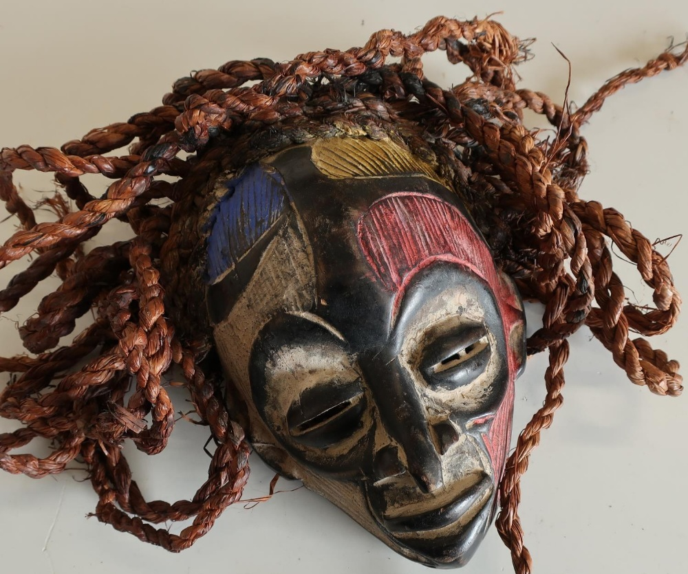 Lot 138 - Small African style carved wood face mask with painted detail and hessian ropework hair