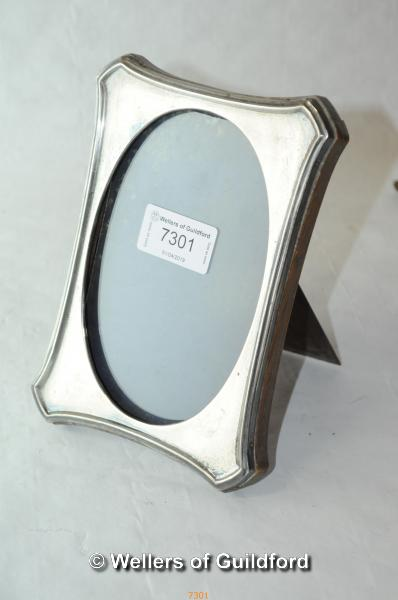 Lot 7301 - An oak backed silver strut photograph frame, 17.5cm tall, marks rubbed.
