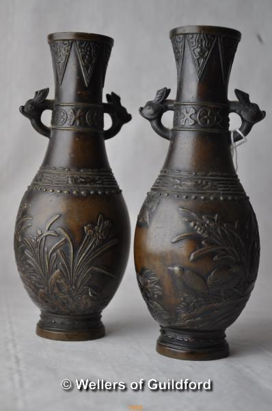 Lot 7524 - A pair of Japanese bronze vases with lug handles, relief moulded with birds amidst foliage, 16.5cm.