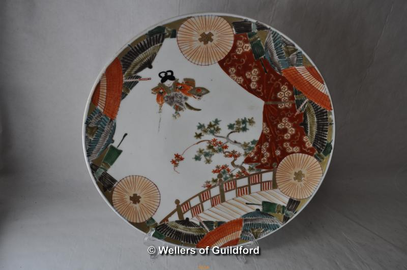 Lot 7493 - A Japanese porcelain plate decorated with a figure, prunus and parasols, 31cm.