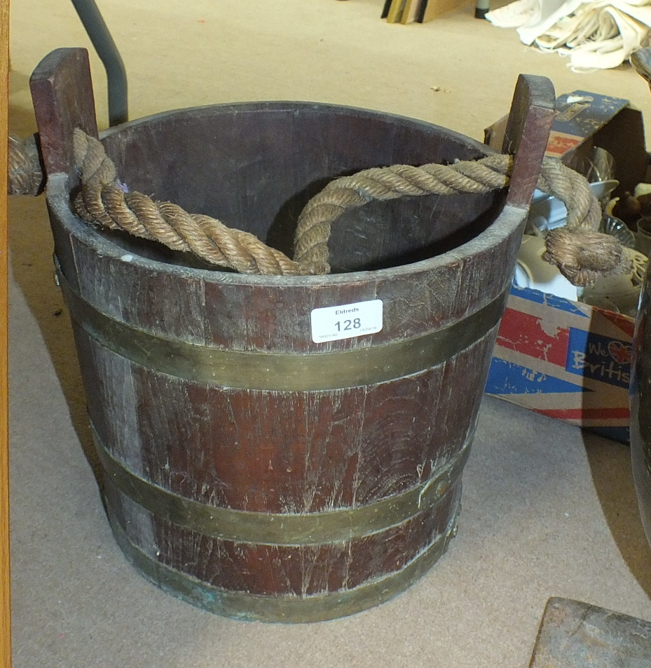 Lot 128 - A brass coopered teak bucket with rope carrying handle, 33cm high, 31cm diameter.