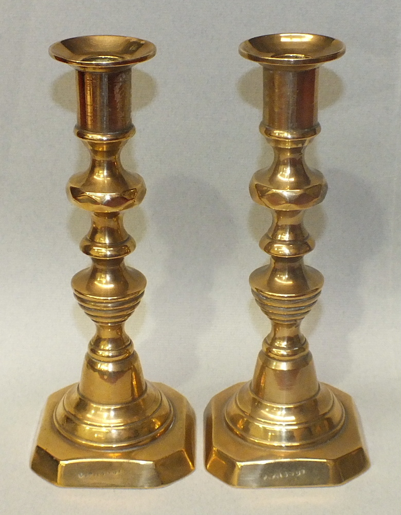 Lot 93 - A pair of 19th/20th century brass candlesticks with candle ejector mechanisms and numbered