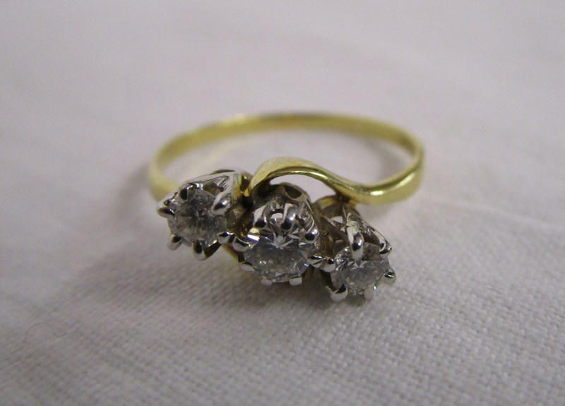 Lot 18 - 18ct gold triple diamond twist ring