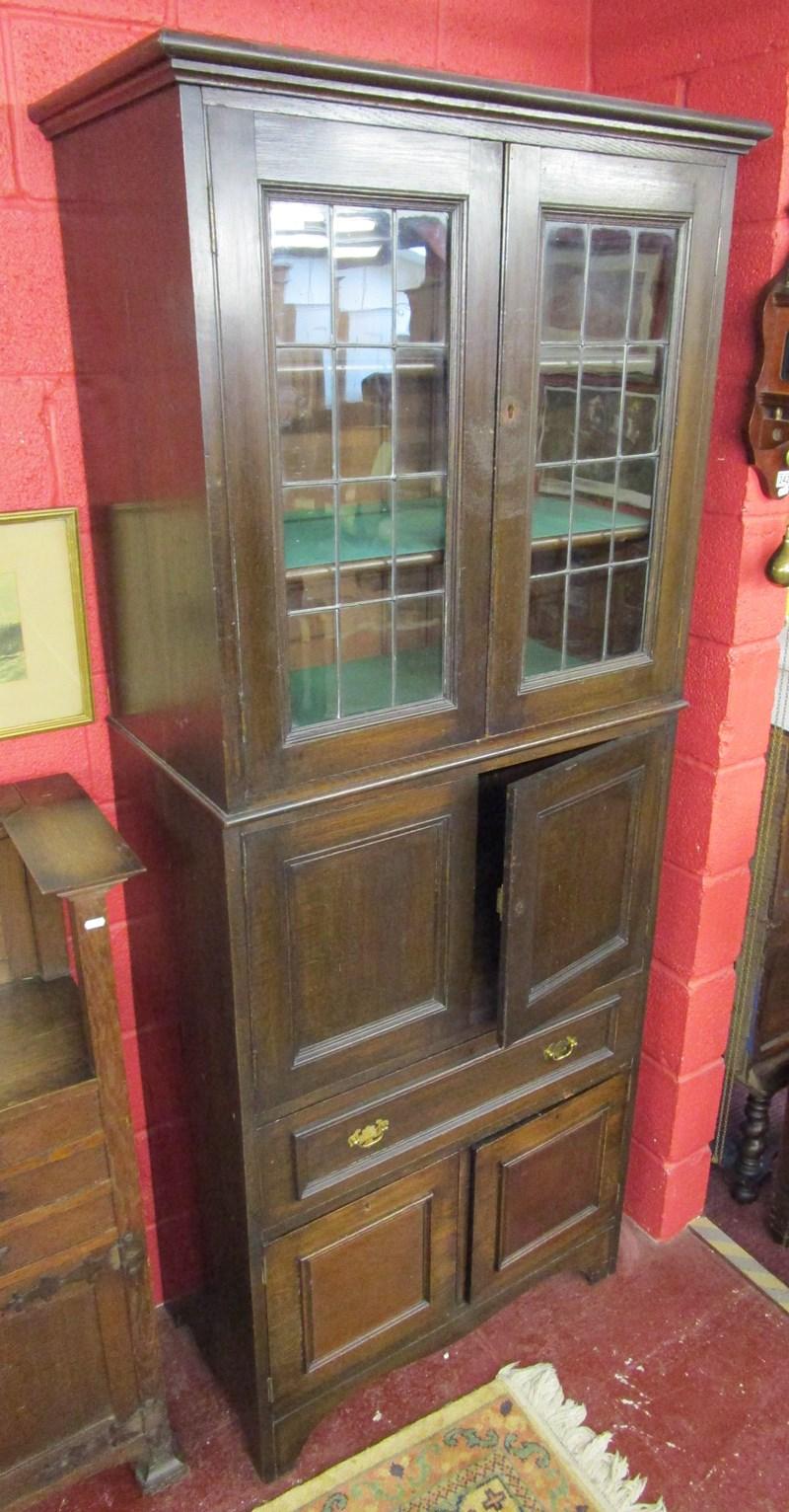 Lot 241 - Tall oak cabinet with glazed doors