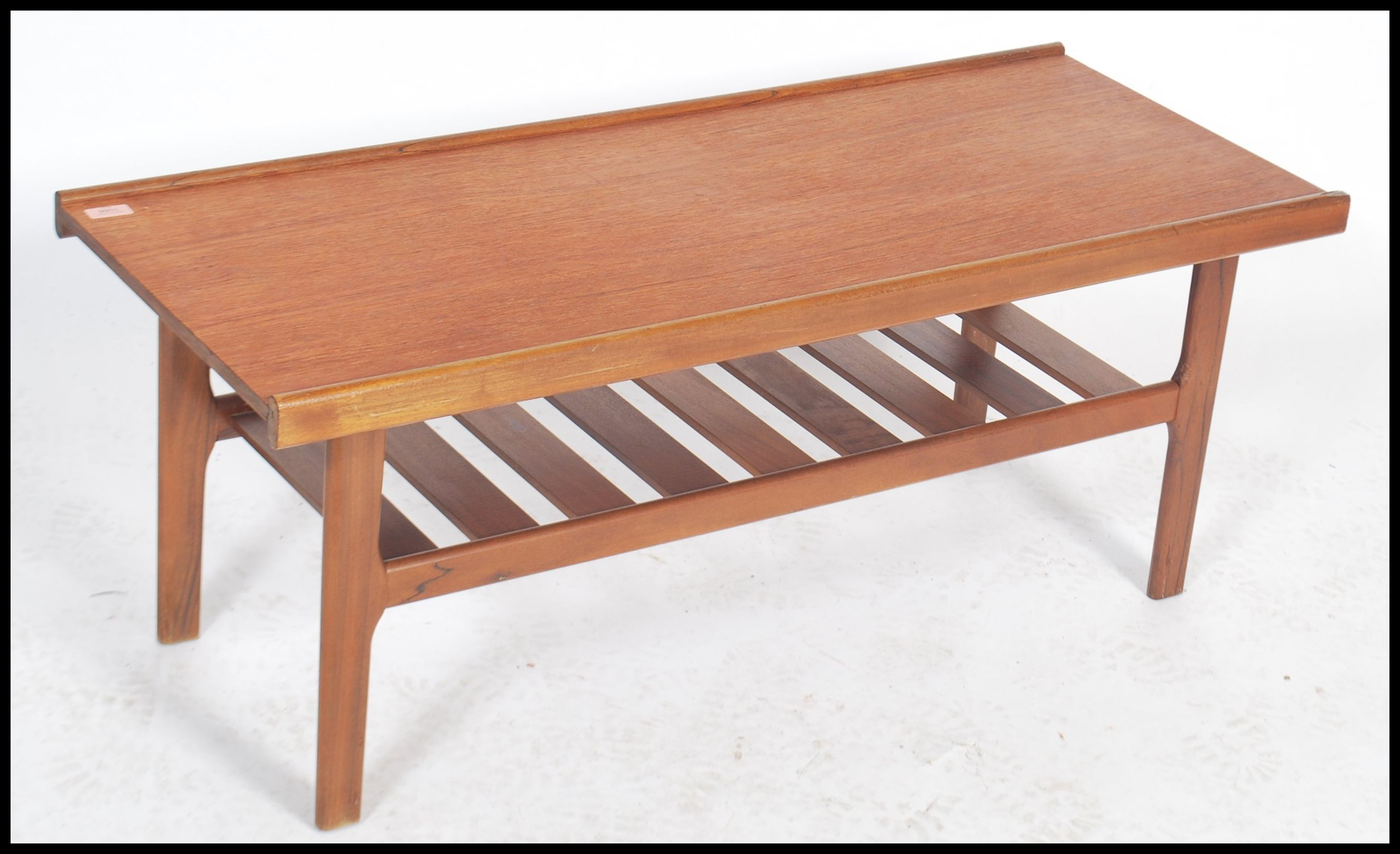 Lot 1066 - A vintage mid century teak wood coffee table with a banded edge rail and magazine rack to the