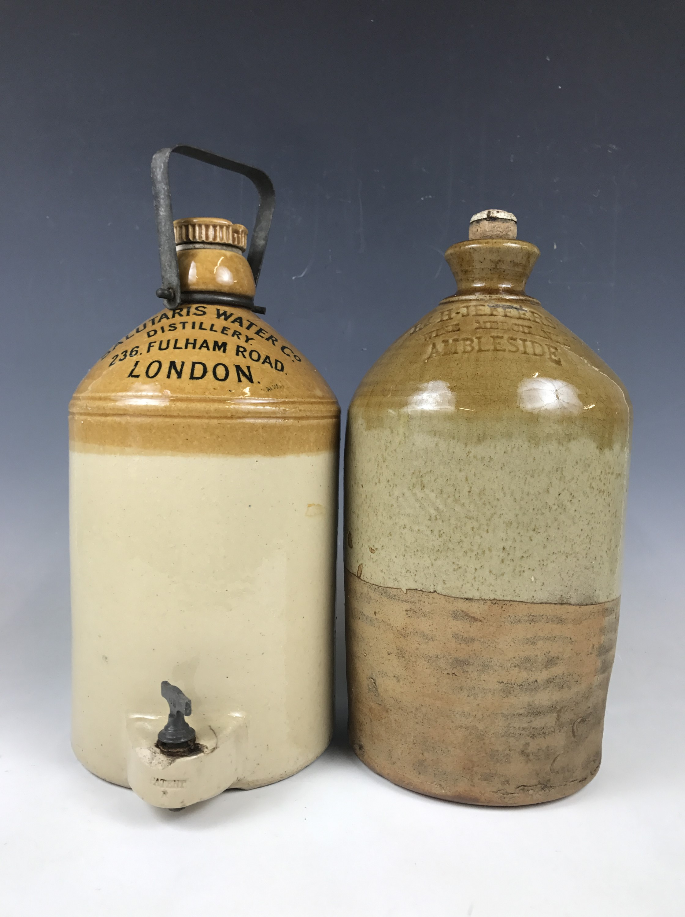 """Lot 58 - A stoneware flagon with tap, printed """"Salutaris Water Co Distillery, 236 Fulham Road, London"""","""
