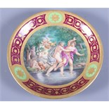 A mid 19th century Vienna porcelain saucer dish, decorated with semi-clad figures and cherubs by a
